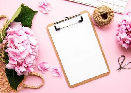 Schönheitskomposition mit Zwischenablage, Hortensie und Zubehör auf rosa Hintergrund. Ansicht von oben. Flach liegen. Home femininer Schreibtisch.