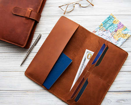 Brown leather travel organizer, pen, map and notebook on a wooden table.
