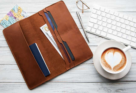 Brown leather travel organizer, pen, map and coffee on a wooden table. Flat lay, top view. Travel concept.