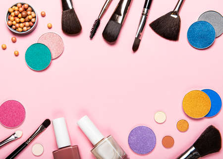 Set of decorative cosmetics on a pastel pink background. Flat lay, top view.