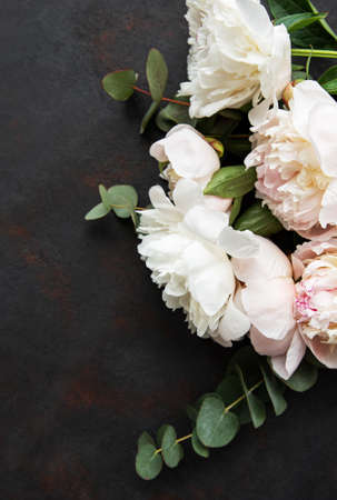 Background with pink peonies on a black concrete background
