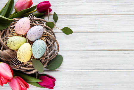 Easter background with colorful eggs in nest and pink tulips on a white wooden background. Top view with copy space Banque d'images