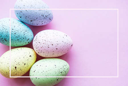 Colorful Easter eggs on pastel pink background. Easter holiday concept, flat lay, top view.