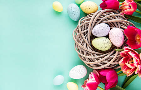 Easter background with colorful eggs in nest and pink tulips on a pastel green background. Top view with copy space Banque d'images