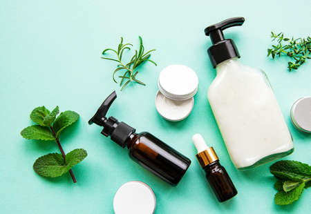 Homemade spa with cosmetic from herbs on pastel  green  background, top view.