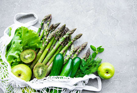 Healthy vegetarian food concept background, fresh green food selection for detox diet,  apple, cucumber, asparagus, avocado, lime,  salad  in mesh bag, top view on a concrete background