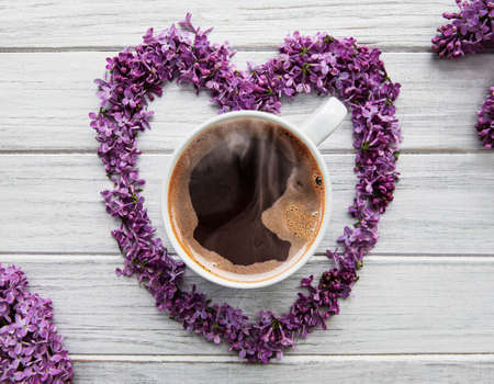 Lilac flowers on a table in the shape of a heart, top view on a cup of coffee Standard-Bild