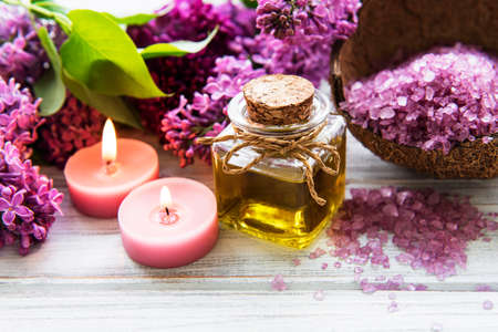 Spa setting with lilac flowers. Sea salt in bowl, bottles with aroma oil  and candles on wooden background.