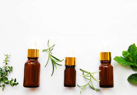 Aromatherapy concept, aroma oil and herbs - mint, rosemary, thyme on a white background, top view Archivio Fotografico