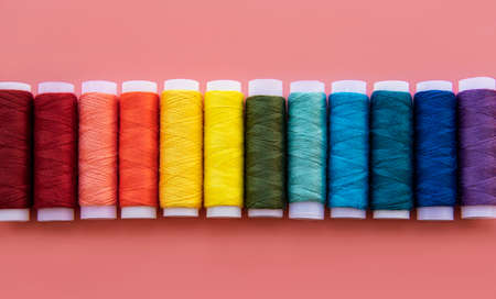 Spools of thread on the colors of the rainbow on a pink background, flat lay