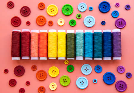 Spools of thread and buttons on the colors of the rainbow on a pink background, flat lay 版權商用圖片