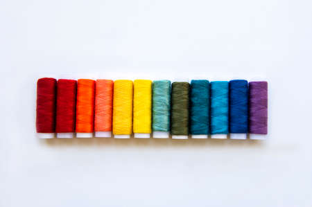 Spools of thread on the colors of the rainbow on a white background, flat lay