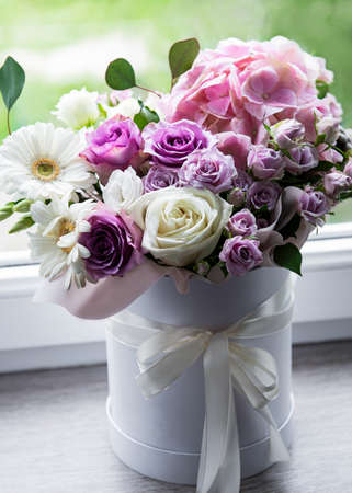 Beautiful flowers. Pink hydrangea and roses in a white round box on the windowsill Zdjęcie Seryjne