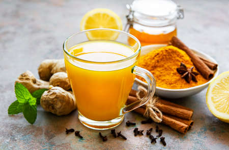 Energy tonic drink with turmeric, ginger, lemon and honey on a gray concrete background Stock fotó