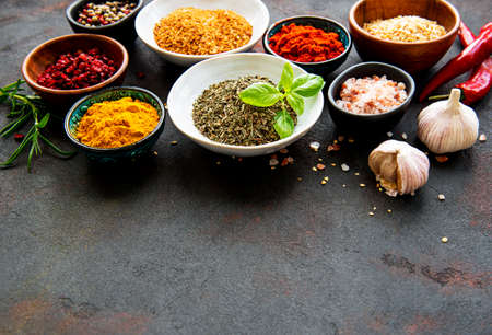 Various spices in a bowls on black concrete background. Top view copy space.