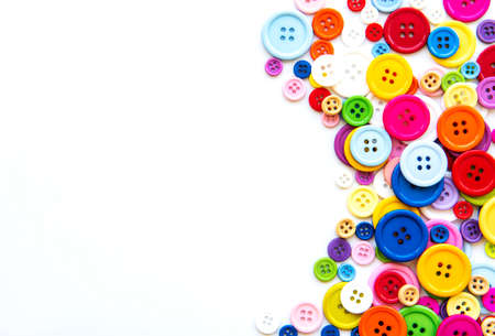 Multicolored sewing buttons on a white pastel background. Sewing border, top view