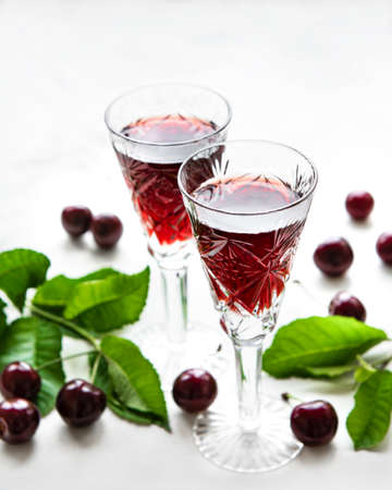Cherry liqueur in a glass and fresh fruit on white marble background