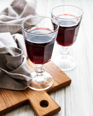 Cherry liqueur in a glass and fresh fruit on a wooden table