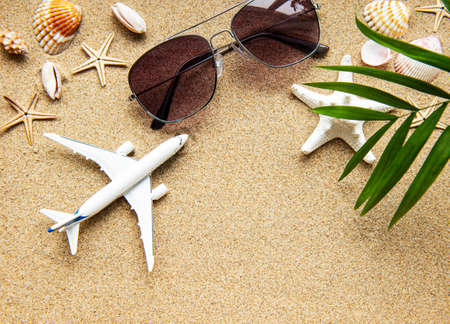 Top view of traveler background on tropical sand, shells and airplane. Background for summer holiday vacation travel trip. Flat lay, copy space