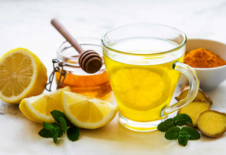 Energy tonic drink with turmeric, ginger, lemon and honey on a white marble background Imagens