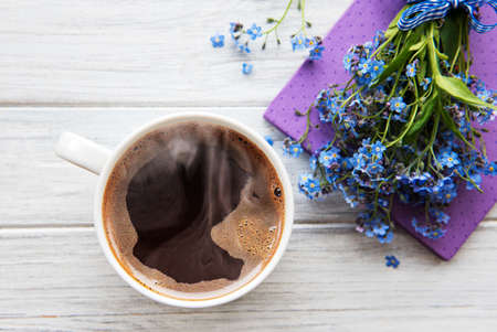 Blue forget-me-not flowers, notebook and a cup of hot coffee. The concept of holidays and good morning wishes. Standard-Bild