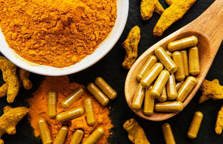 Turmeric powder and turmeric pills on a black concrete background Imagens