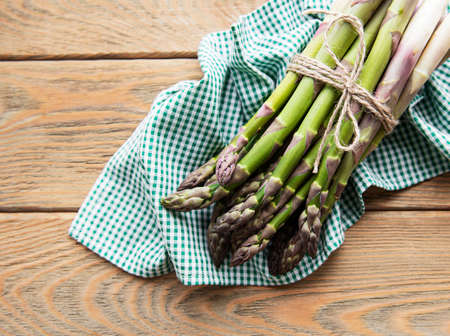 Fresh green asparagus on old wooden table. Flat lay