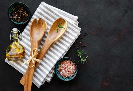 Old vintage kitchen utensils. Wooden spoons, cutting board, napkin and spices over black background. Top view 免版税图像