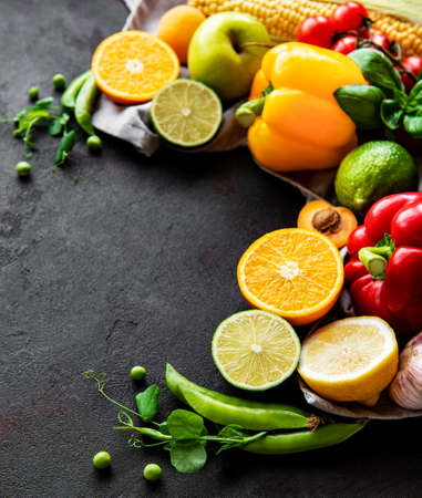 Healthy food. Vegetables and fruits on a black concrete background. Top view. Copy space.