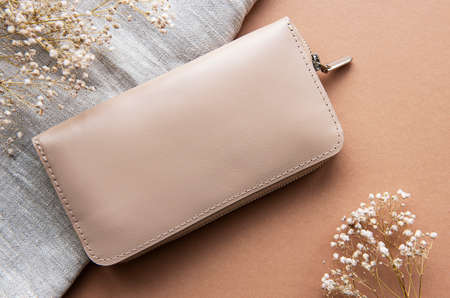 Beige leather wallet on a brown background