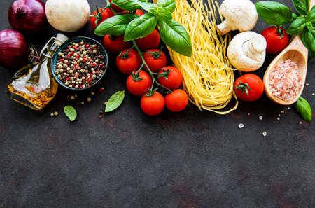 Healthy mediterranean diet, ingredients for Italian meal, spaghetti, tomatoes, basil, olive oil, garlic, peppers on black background
