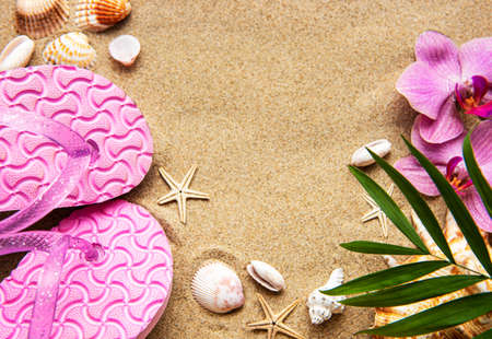 Flip Flops in the sand with starfish and orchid flowers. Summertime on beach concept. Summer beach. Standard-Bild