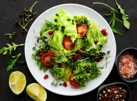 Fresh green mixed salad bowl with tomatoes and microgreens on black concrete background. Healthy food, top view. Stock fotó
