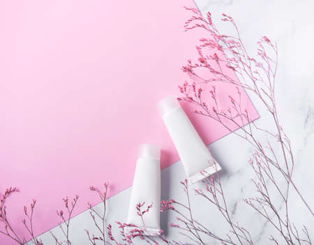 White tubes of cream on a marble and pink background and decorative branch Banque d'images