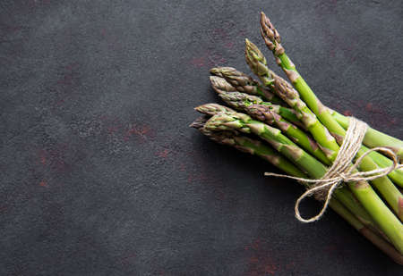 Fresh green asparagus on black concrete background. Flat lay