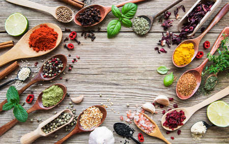 A selection of various colorful spices on a wooden table in spoons Foto de archivo