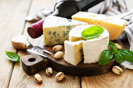 Various types of cheese, grapes, wine and snacks on a old wooden background