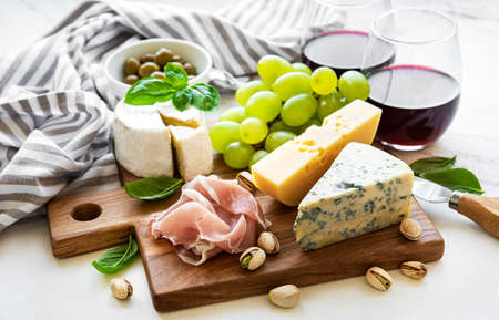 Various types of cheese, grapes, wine and snacks on a white marble background