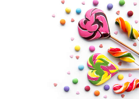 Multicolored candies, dragees and lollipops on a white background