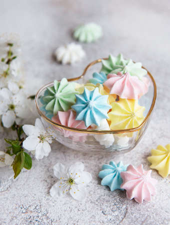 Small colorful meringues in the heart shaped bowl on concrete background
