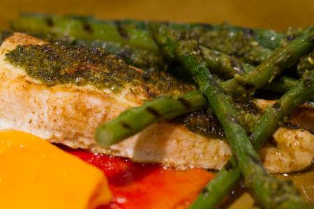 Gebakken zalm met asperges en paprika bedekt met peterselie en knoflook Stockfoto