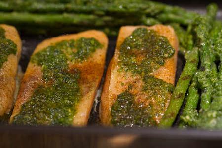 Gebakken zalm met asperges en paprika's bedekt met peterselie en knoflook