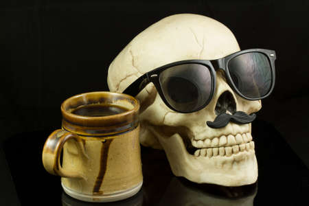 eye socket: Skull wearing Hipster glasses and a mustache, having a cup of coffee Stock Photo