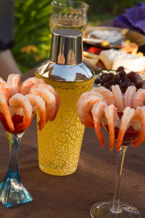 Shrimp cocktail on martinin glasses with cocktail shaker in the background