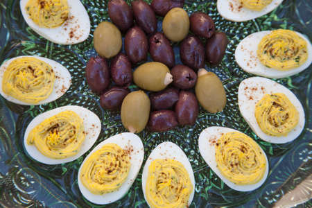 deviled eggs: Marinated Kalamata olives and green olives stuffed with garlic served with deviled eggs sprinkled with paprika Stock Photo
