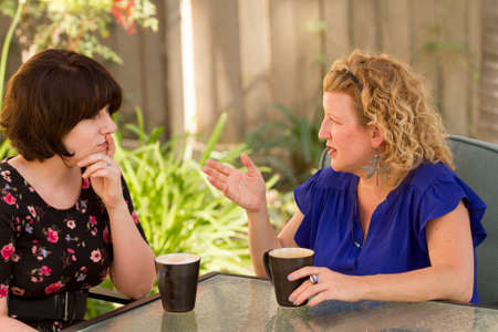 Women and friendship sharing stories over a cup of coffee outdoors