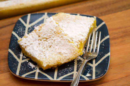 Lemon Bar serving freshly backed and covered in powdered sugar.  Served on a blue and white plate