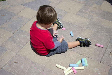 pavers: Little boy playing with chalk on cement pavers Stock Photo
