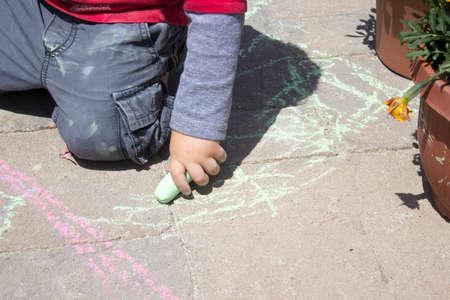 adoquines: Ni�o peque�o que juega con tiza en adoquines de cemento Foto de archivo