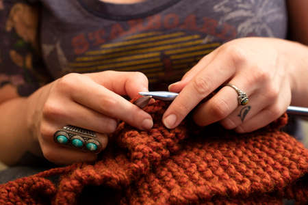 Young woman knitting a scarf with maroon yarn. Stok Fotoğraf